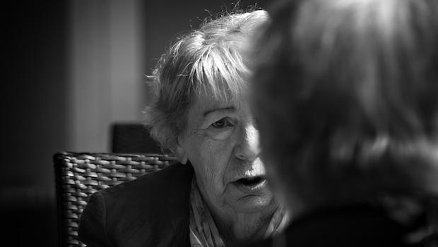 Gesicht einer älteren Frau und Hinterkopf einer anderen Person