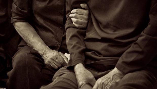 älteres Paar sitzend Hände