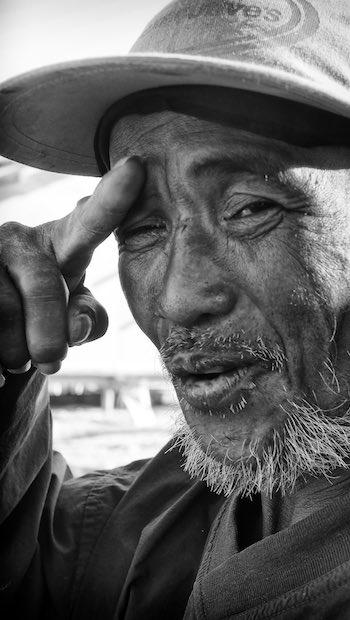 älterer Mann mit Hand zum Gruß und Basecap