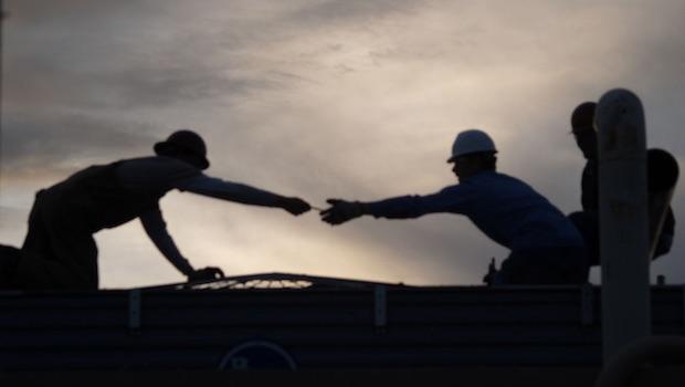 Arbeiter mit Helmen reichen sich etwas