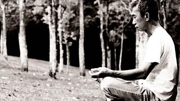 Asiate im Yogasitz im Wald schwarz weiß
