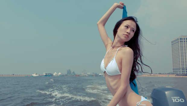 Asiatin auf Boot im Bikini