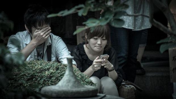 asiatische Paar, sie blickt auf ihr Smartphone, er hält die Hand vors Gesicht