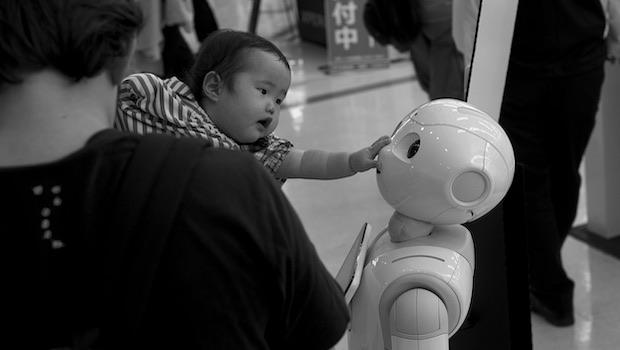 Baby berührt Gesicht von Roboter