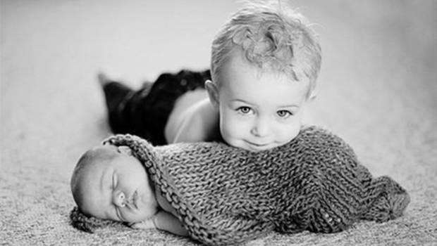 Baby und Kleinkind auf Teppich kuschelnd