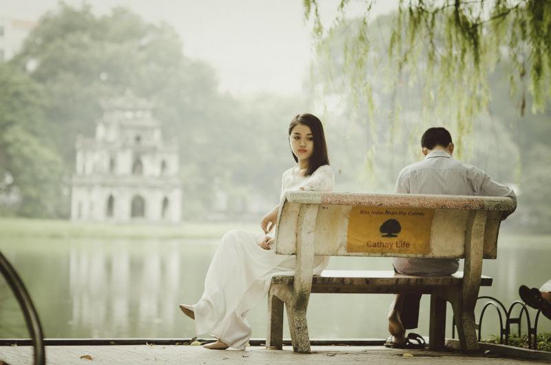 Frau sitzt abgewendet von Partner auf einer Bank.