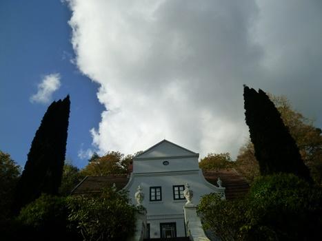 Haus mit Spitzdach, Ansicht von unten, zwei Bäume bilden Portal