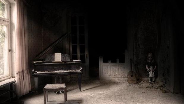 Mädchen mit Puppe in der Ecke eines verlassenen Zimmers