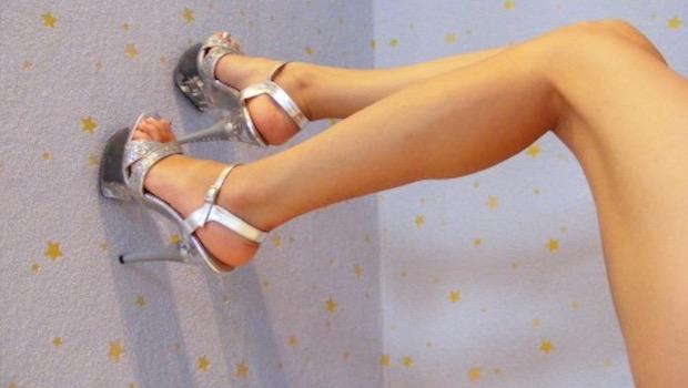 Frauenbeine mit Pumps, weiße Wand mit Sternen