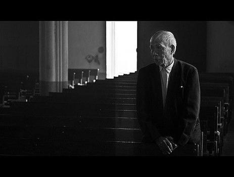betender alter Mann in Kirche, schwarzweiß