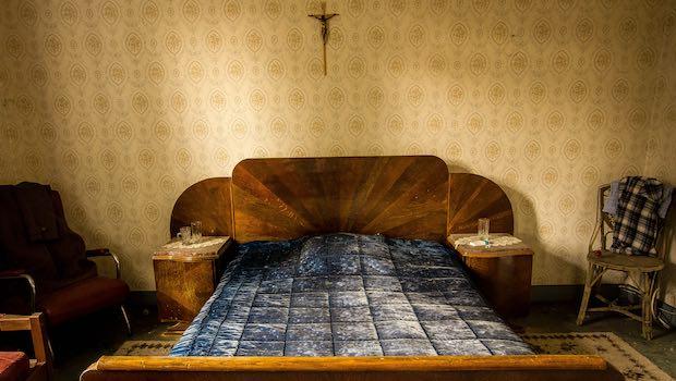Bett im Zimmer schmutzige Tapete, Kreuz, Stuhl