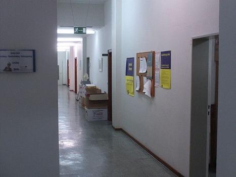 Büroflur mit Neonlicht und Pinwand