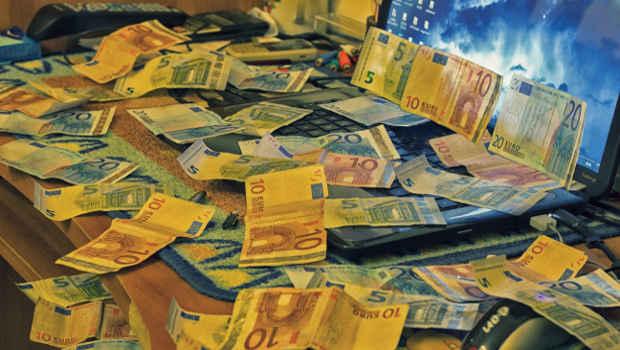 Geldscheine vor Computer auf Schreibtisch