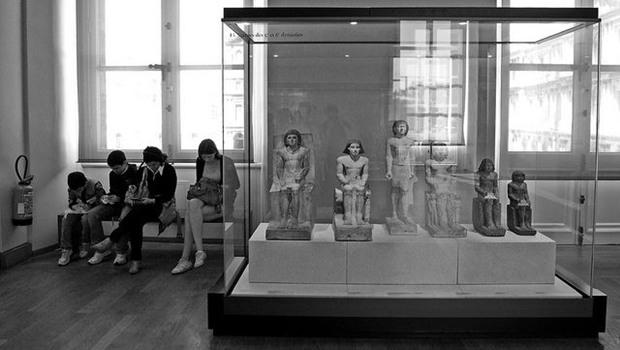 Museumsbesucher sitzen neben sitzenden Puppen in Vitrine, schwarzweiß