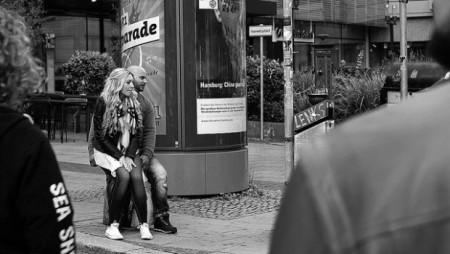 Junge Frau sitzt auf Bein von Mann vor Litfasssäule, schwarzweiß
