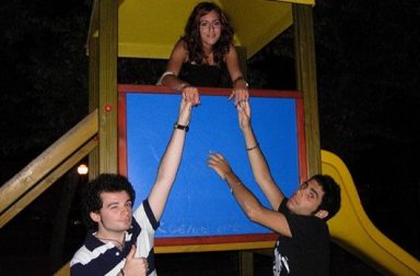 junge Frau auf Spielzeug reicht zwei Männern die Hand