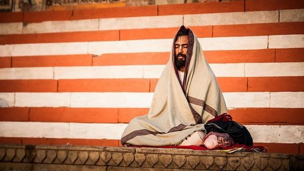 Yogi in Decke gehüllt, rot-weiß gestreifte Wand