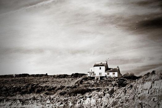 Häuser in karger Landschaft, schwarzweiß
