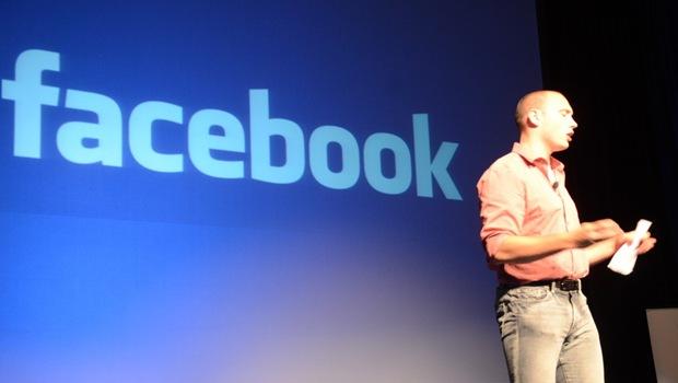 Mann auf Bühne vor facebook Schrift