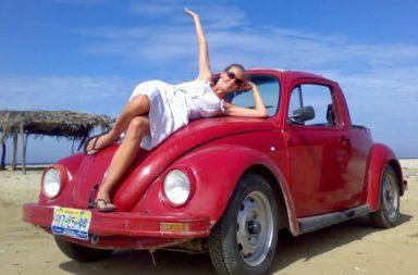 Frau auf rotem VW Käfer
