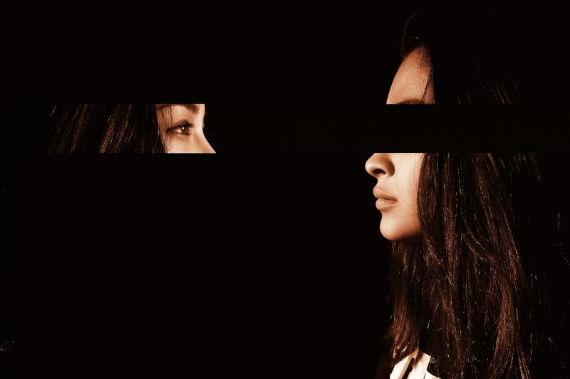 Augenpartie der Frau ist auf dem Foto verdeckt. Die Augenpartie spiegelt sich gegenüber.