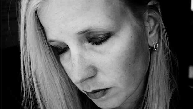 Frau blond zwei Ohrringe traurig