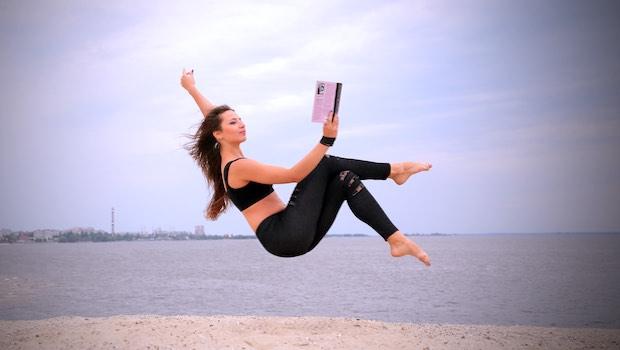 Frau mit Buch in Luft schweben