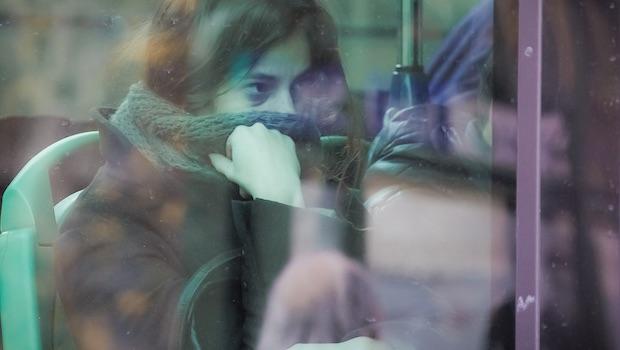 Frau im Bus Schal vorm Mund