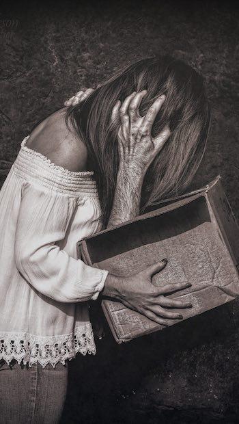 Frau schaut in Karton mit Männerhand