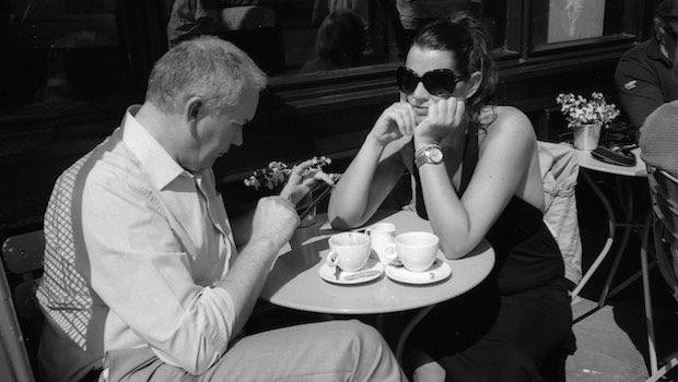 Frau und Mann am Tisch er schaut aufs Handy