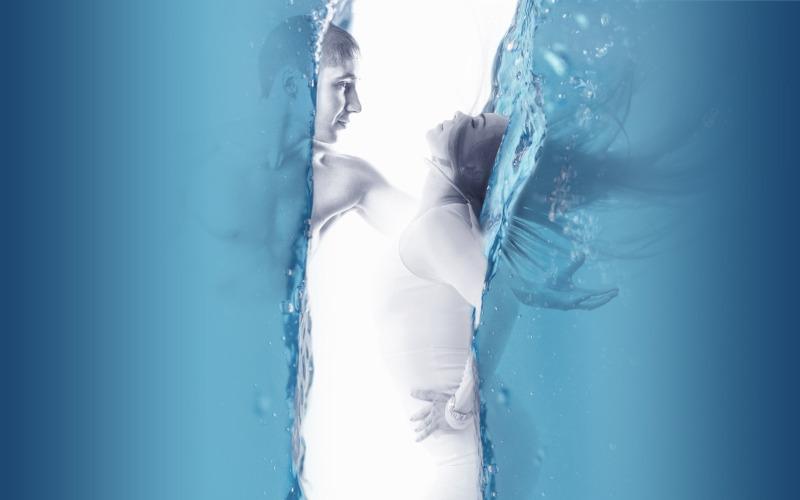 Frau und Mann jeweils in Wasserwänden bewegen sich zueinander.