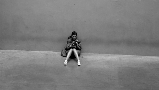 Frau sitzend vor Mauer mit Handy