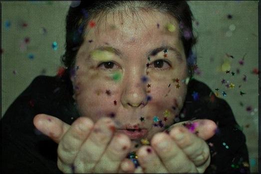 asiatsiche Frau pustet Konfetti