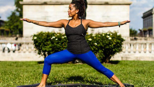 Frau im Park Yoga Kriegerposition