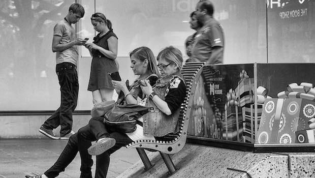 Frauen auf Bank mit Handys Menschen im Hintergrund