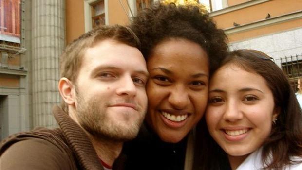 bärtiger Mann, farbige Frau und Frau Wange an Wange
