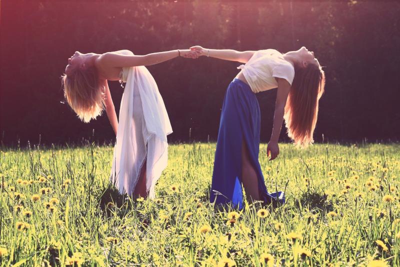 Zwei junge Frauen halten sich fest. Sie stehen auf einer Wiese.