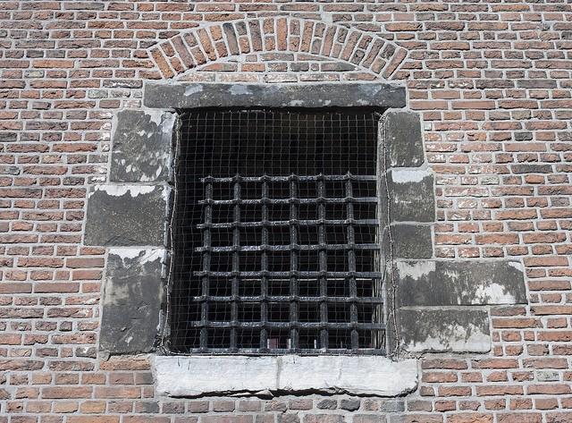 vergittertes Gefängnisfenster in roter Backsteinmauer