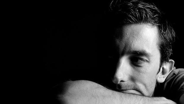 gelangweilter Mann, Kopf auf Arm, schwarzweiß