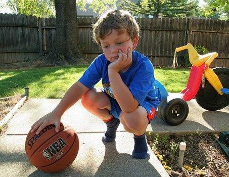 Junge gelangweilt, hockt mit Ball