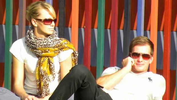 junges Paar mit Sonnenbrillen, sie sitzend, er liegend