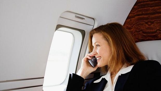 Frau mit Handy im Flugzeugsitz
