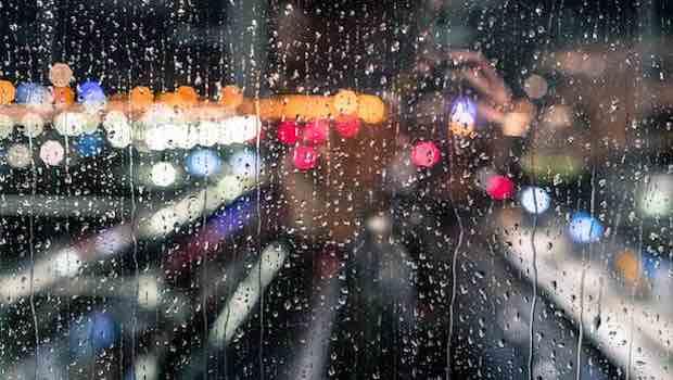 Glasscheibe mit Regentropfen dahinter bunte Lichter