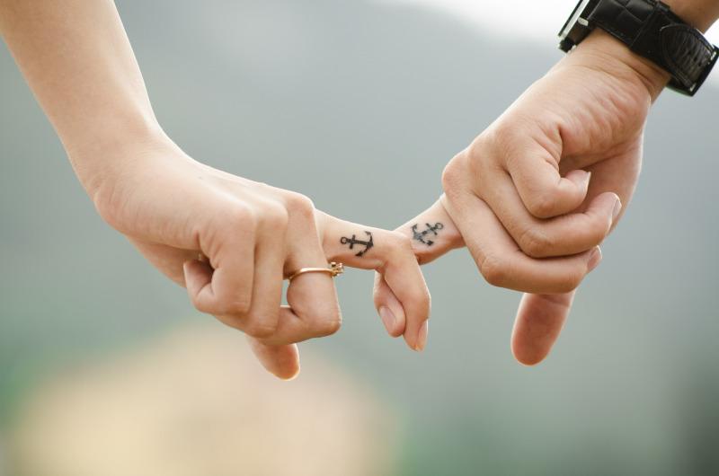 Pärchen hat Zeigefinger verhakt. Beide haben darauf dasselbe Tattoo.