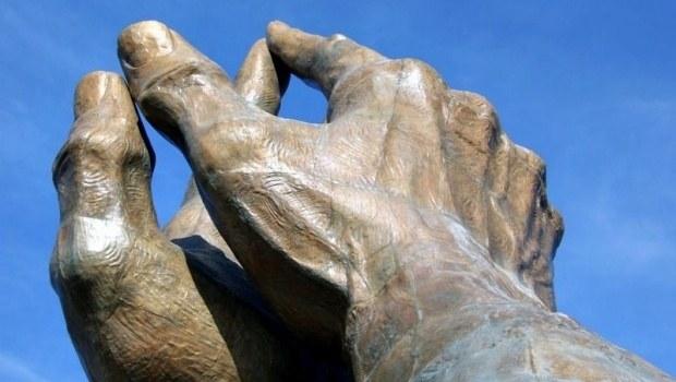 Steinskulptur zweier Hände vor blauem Himmel