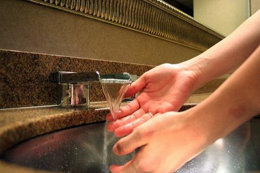 Händer unter fließendem Wasserkran