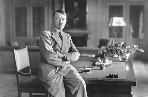 Hitler auf Schreibtisch sitzend