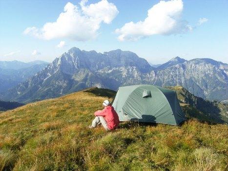 Mann sitzt neben Zelt auf Gebirgswiese