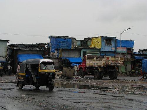 Slum mit Wellblechhütten, LKW, Dreirad