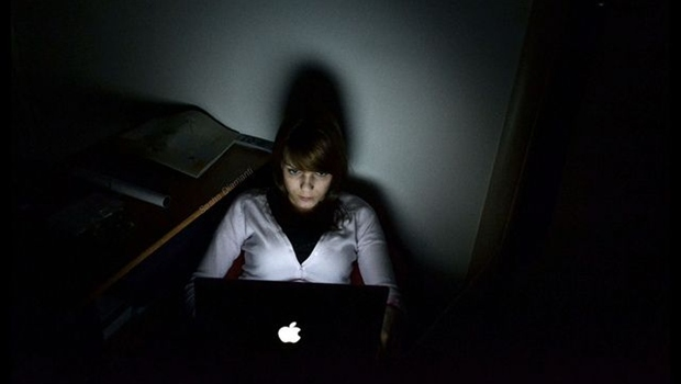 Frau in dunklem Zimmer vor Laptop